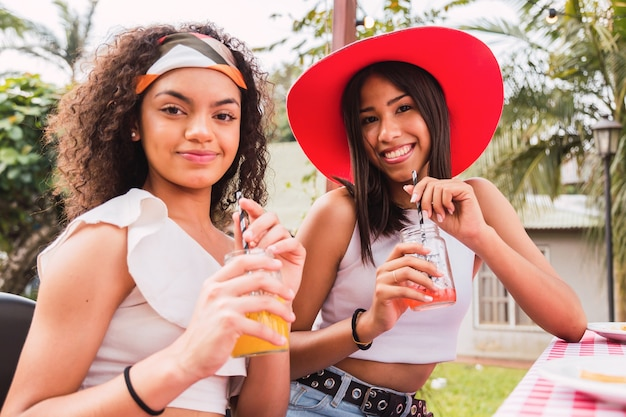 Молодые девушки наслаждаются днем, пьющим сок