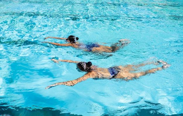 スイミングプールを楽しんでいる若い女の子