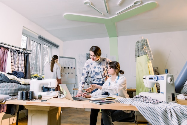 Young girls fashion designers using modern laptop and drawing sketches for new collection of clothes while working at table in studio. woman dressmaker taking mannequin measurements with measure tape