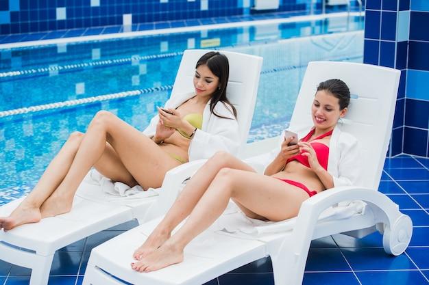 그녀의 스마트 폰에 친구와 메시징 어린 여자 친구. 휴식 스파 및 기술 소셜 네트워크 개념입니다.