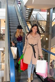 ショッピングセンターのエスカレーターで幸せでたくさんのバッグを持って降りる若い女の子