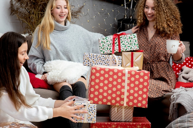 집에서 재미 포장 선물을 가진 어린 소녀, 크리스마스 선물을 포장하는 친구의 팀워크