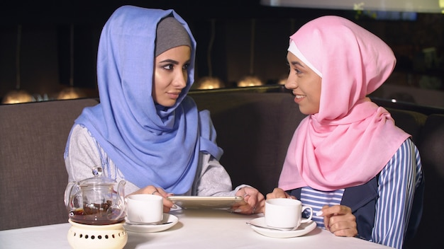 Young girls in hijabs spend time together.