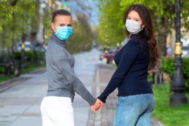 保護医療マスクで手をつないでいる若い女の子。同性関係の概念、lgbtの人々、レズビアン、エピデミック、ウイルス、コロナウイルス