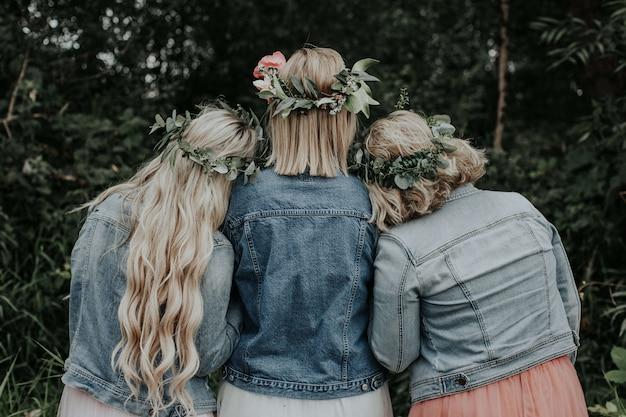 Молодые девушки в красивых платьях и джинсовых куртках в парке
