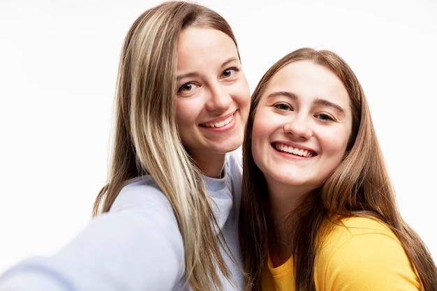 明るいtシャツを着た若い女の子は、自撮りして笑います。関係と友情。閉じる。