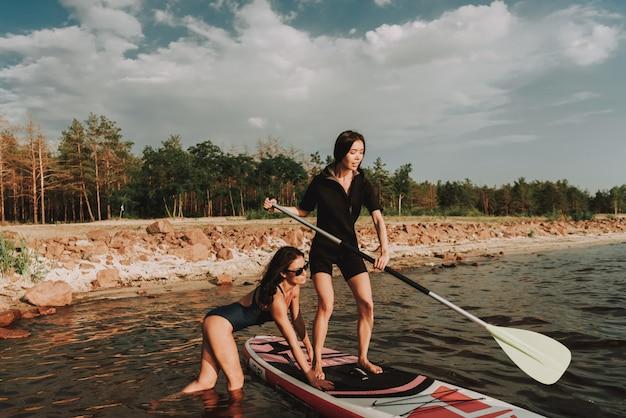 Молодые девушки в гидрокостюм гребли серфинга с веслом.