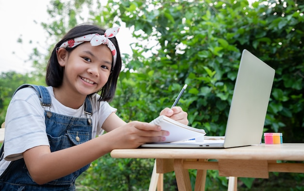 Young girls learn about online lessons by laptop in the front yard.