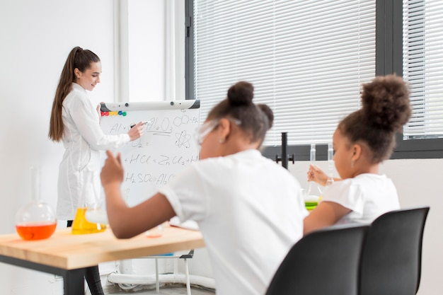 Young girls learning about chemistry from female scientist