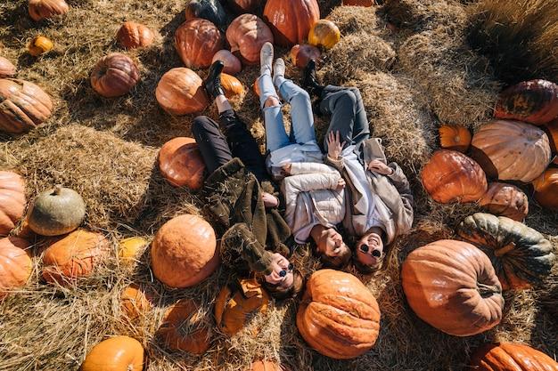 Молодые девушки лежат на стогах сена среди тыкв. вид сверху