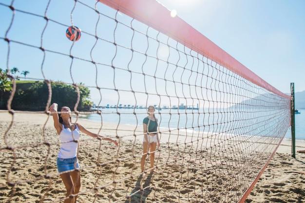 Молодые девушки играют в зал на пляже