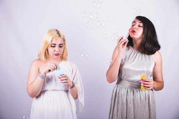 Молодые девушки играют с пузырьками