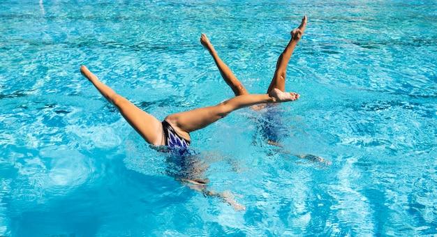 Молодые девушки позируют в бассейне