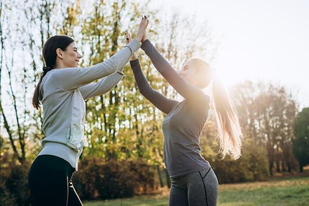 Молодые девушки поднимают руки вверх, совместно выполняют гимнастические упражнения, зачатие о здоровом образе жизни.