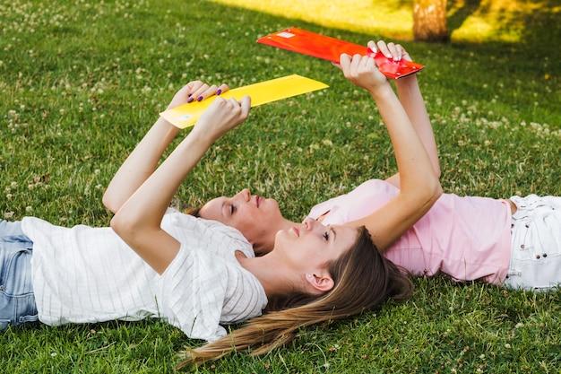 Молодые девушки читают учебники pn газон