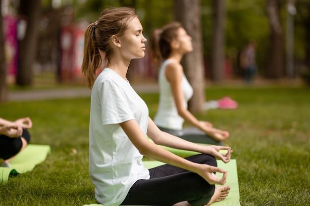 Молодые девушки сидят в позах лотоса и занимаются йогой на ковриках для йоги на зеленой траве в парке в теплый день.