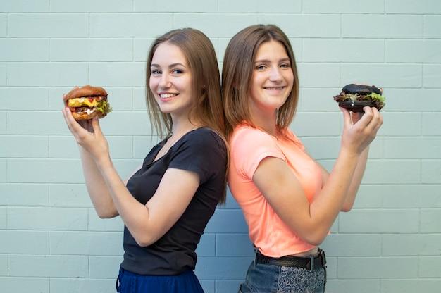 ハンバーガーを食べて立つ若い女子学生