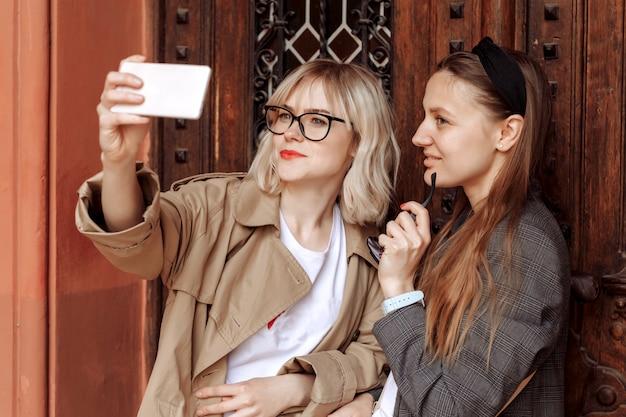 電話でselfiesを取っている若い女の子。通りの壁にあるスマートフォンのソーシャルメディアの自分撮り写真。驚きの顔、感情。