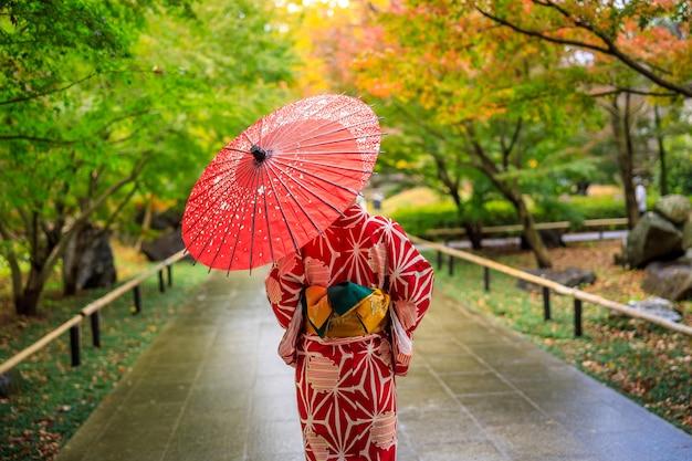 赤い着物と傘を着た若い女の子の観光客が日本の秋の公園で散歩しました。