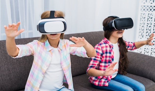 Young girls using a virtual reality headset touching their hands in the air