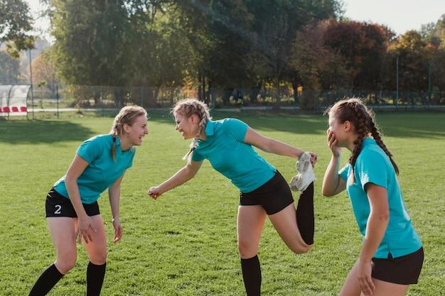 サッカーのピッチでウォーミングアップの若い女の子