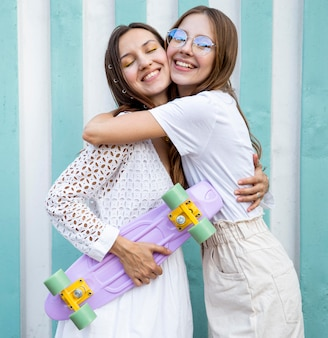Young girls with skateboard hugging