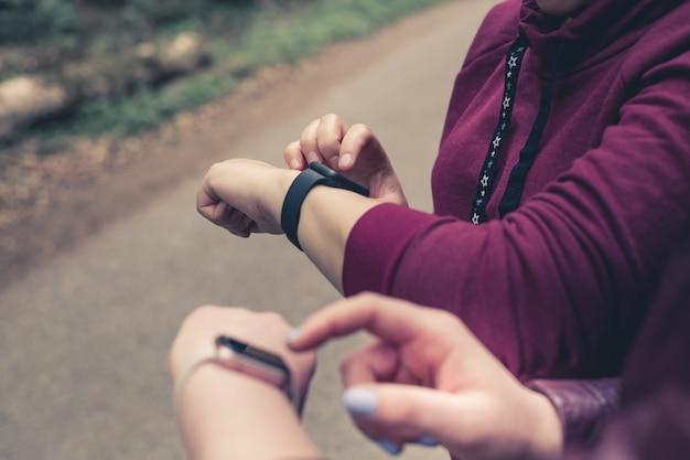 手にスマートウォッチ、現代の技術を持つ若い女の子