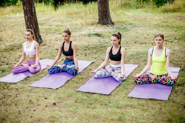 Young girls yoga in the park. relax in nature.