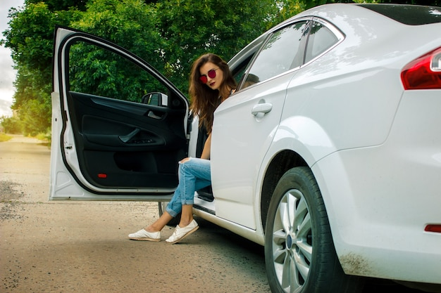 Young glamorous lady with glasses sits in a big beautiful white car