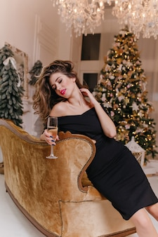 Young and glamorous woman, with very beautiful hair tilted to side and with red lipstick on her lips, is sitting on velour sofa, touching her neck.