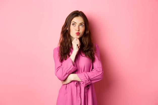 若い魅力的な20代の女性のパッカーの唇は物思いにふけり、あごに触れ、考えながらコピースペースを見上げ、アイデアを考え、ピンクの壁に立ち向かいます。