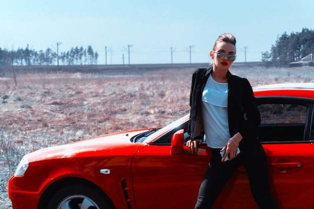 Young glamour lady in mirror sunglasses near a red sports car in the field