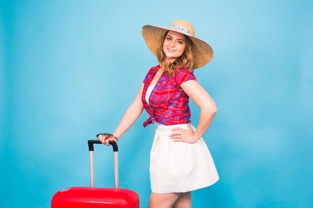赤いスーツケースを持つ若い魅力的な女性。旅行、休日、人々のコンセプト。