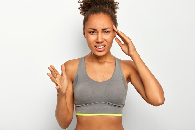 Young gloomy sportswoman touches temple, suffers from migraine and dizzy, gestures with hand, dressed in top, has slim figure, being tired, poses indoor against white background