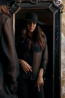 ヴィンテージミラーに立っているスタイリッシュな黒の衣装を着た若い栄光のモデル