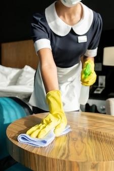 Молодая женщина в перчатках в униформе, стирающая деревянный стол с моющим средством