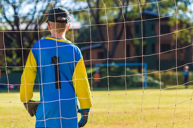 Young goalkeeper boy standing guard in front of his team goal during a game