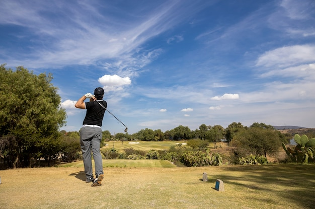 Young golf player hitting the ball, blue sky