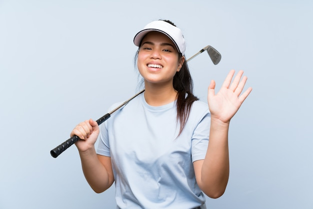 Young golfer asian girl over isolated blue wall saluting with hand with happy expression