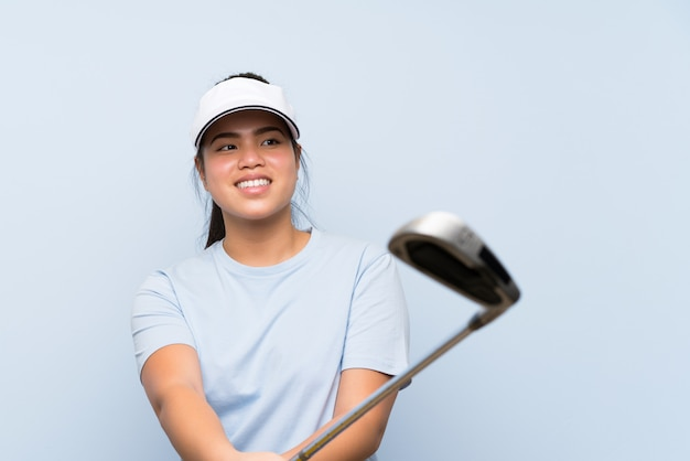 Young golfer asian girl over isolated blue wall