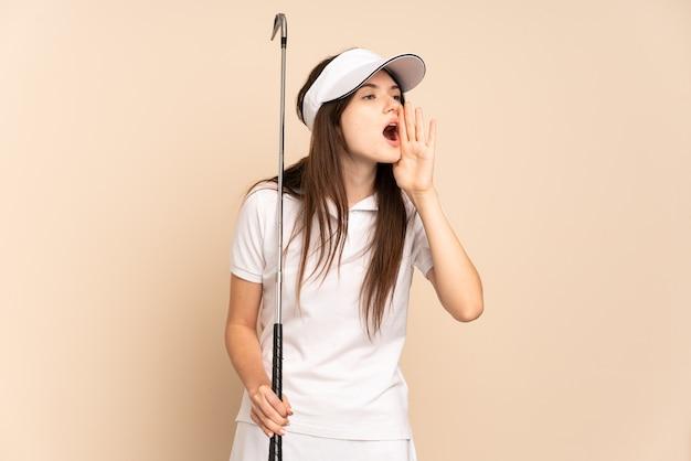 Молодая девушка в гольф изолирована на бежевом и кричит с широко открытым ртом