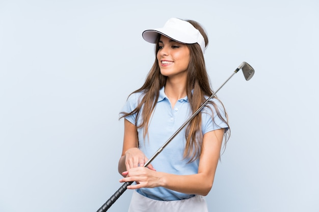 Young golfer woman over isolated blue wall smiling a lot