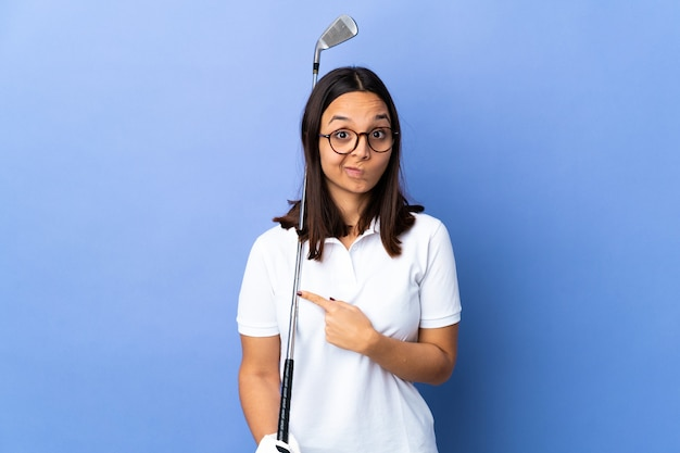 Young golfer woman over isolated colorful background pointing to the laterals having doubts