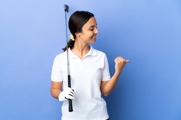 Young golfer woman over isolated colorful background pointing to the side to present a product