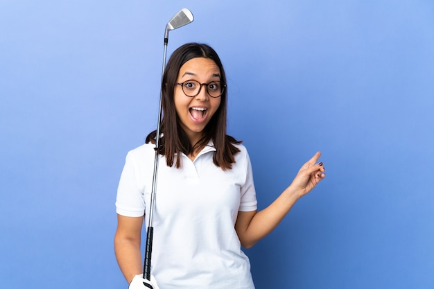 Young golfer woman isolated surprised and pointing side