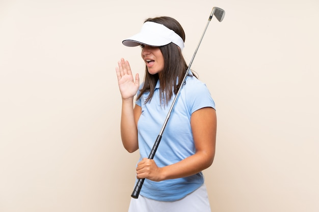 Young golfer woman over isolated wall shouting with mouth wide open
