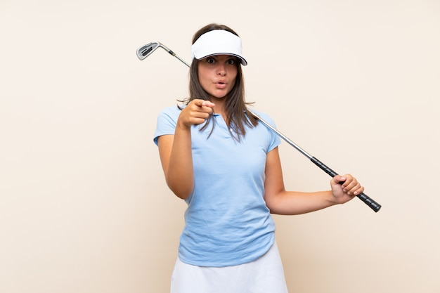 Young golfer woman over isolated wall surprised and pointing front