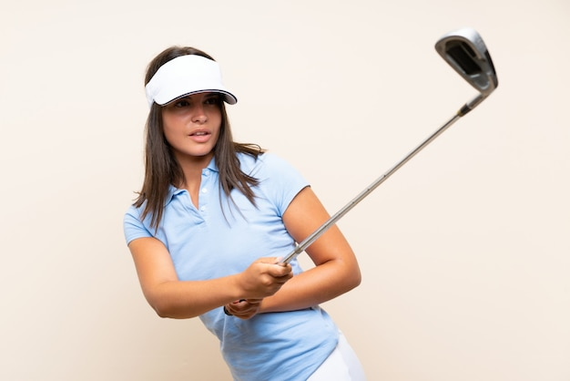 Young golfer woman over isolated wall