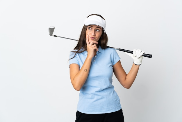 Young golfer woman over isolated white background having doubts while looking up