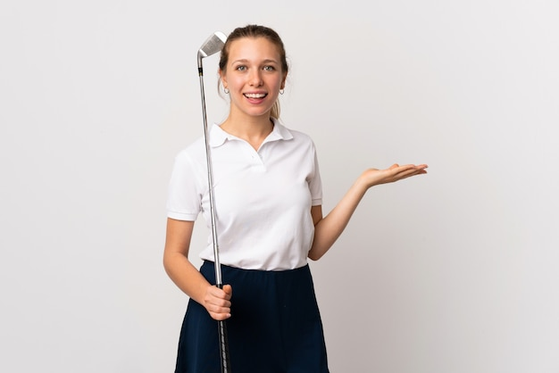 Young golfer woman over isolated white wall holding copyspace imaginary on the palm